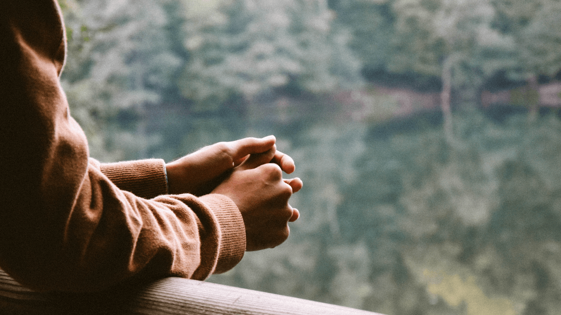 Hands resting on a railing overlooking a river