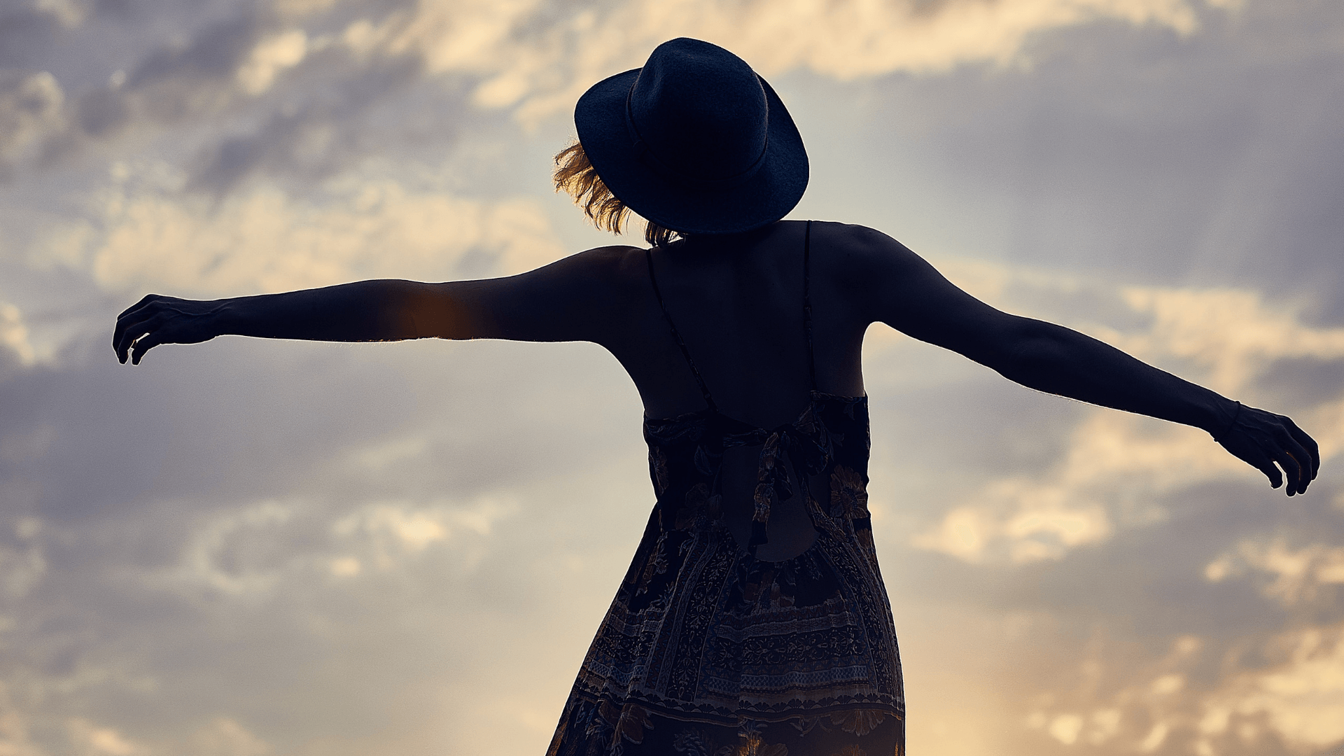 Woman dancing outside during sunset
