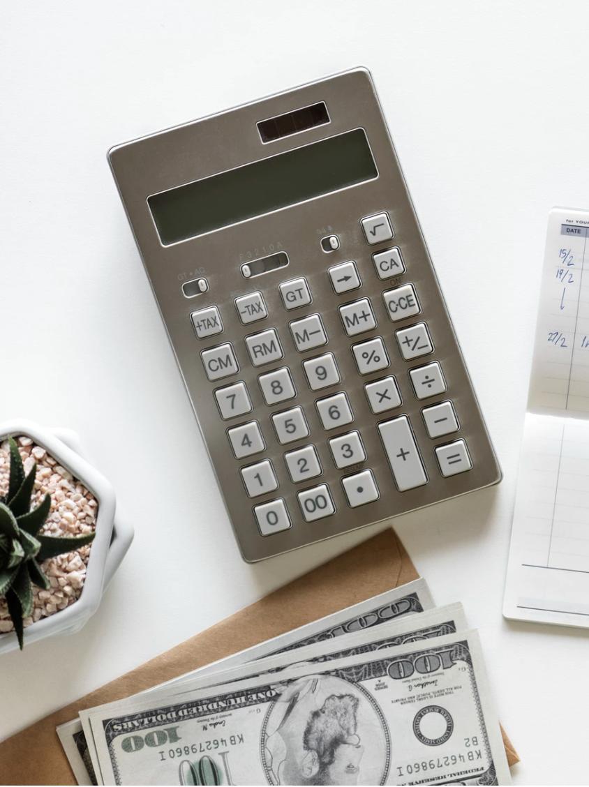 calculator beside hundred dollar bills