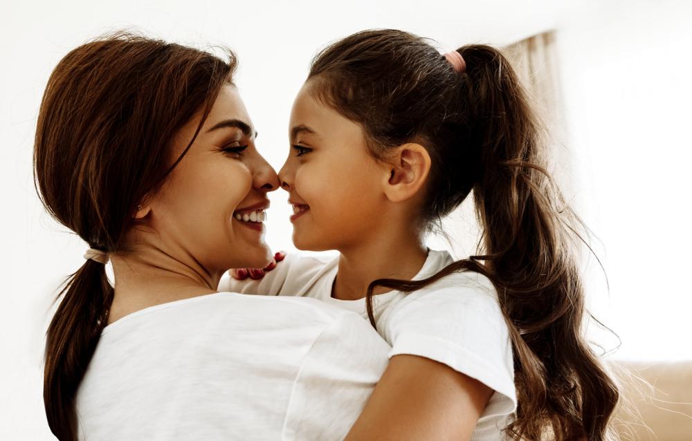 Mother hugging daughter keeping her secure