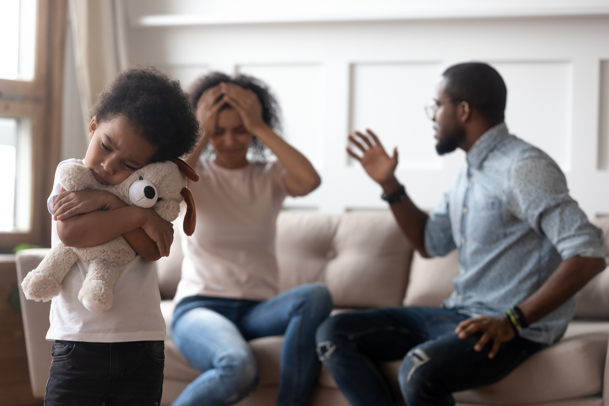 Son holding teddy bear while her parents argue